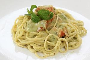 Spaghetti and salmon in pesto sauce photo