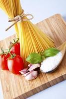 Whole wheat spaghetti and vegetables on wooden tabletop photo