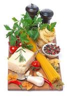 spaghetti, Parmezaanse kaas, specerijen en verse kruiden op een houten bord