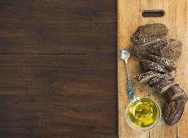 Dark baguette cut in slices with olive oil photo