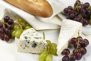 Französische Tafel mit Baguette, Weintrauben und Käse