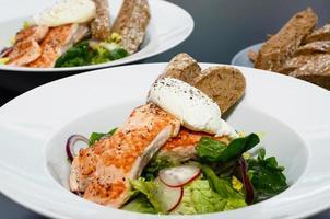ensalada de salmón con huevo benedicto, servido con baguette