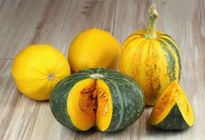 Assorted pumpkins and squashes on rustic wooden board