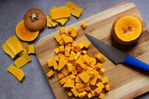 Chopping butternut squash into cubes on a wooden cutting board