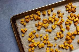 Roasted butternut squash cubes on parchment paper lined baking tray