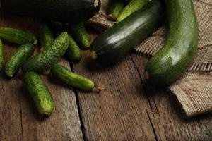 Zucchini and cucumbers on wooden background.