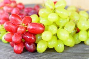 uvas naturales verdes y rojas en una placa de madera foto