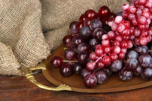 Golden tray with grape on wooden background photo