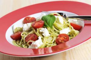Pasta Spaghetti with Pesto and Tomatoes Goat Cheese Red Plate photo