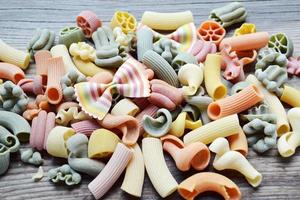 Different kinds of colorful Italian pasta on wooden table