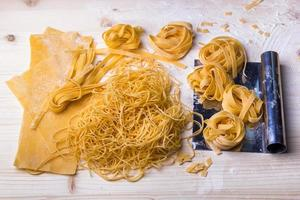 Homemade noodles and pasta on wooden table