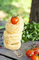 Raw pasta with parsley and onion on table