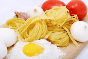 espagueti, huevos, cebolla, ajo y tomate en plato de madera foto