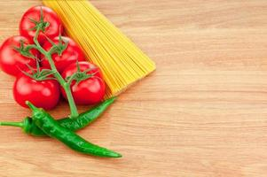 Bunch of spaghetti pasta, green hot peppers and Ripe tomatoes photo
