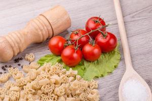 pasta, tomate y pimiento sobre un fondo de madera