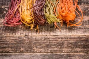 Various mix of pasta on wooden rustic background.