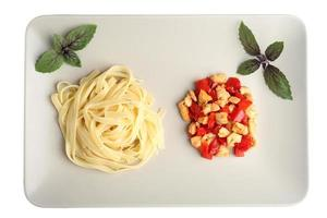 Pasta with grilled chicken and peppers in a plate.