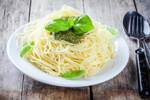 Spaghetti with pesto sauce and basil photo