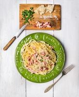 spaghetti carbonara in green plate on white wooden background photo
