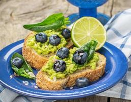Avocado sandwich and blueberry on the wooden background photo