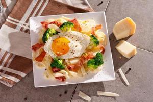 Tagliatelle pasta with broccoli, prosciutto and fried egg.