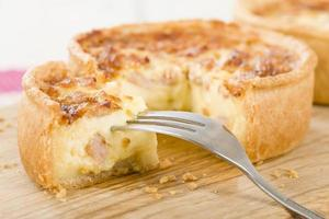 Close up of quiche with fork on wooden board