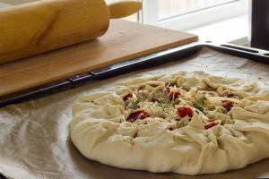 rustic homemade pie with feta, sun-dried tomatoes