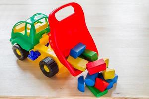 Toy car truck dumping bricks, wood background