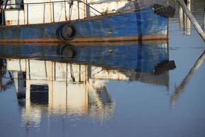 Casco azul oxidado del barco de pesca que refleja en el agua foto
