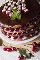Cherry cake with chocolate and cream close-up vertical photo