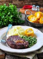Rare beef steak with mashed potatoes, green peas, boiled corn photo