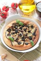 Vegetarian pizza with eggplants, olives and pine nuts photo