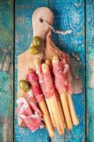 breadsticks with prosciutto and olives photo