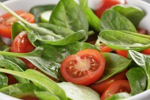 Ensalada orgánica fresca de verano con tomates, pepinos y espinacas foto