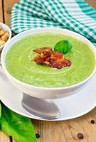 Soup puree with bacon and spoon on board photo