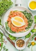 Raw salmon in white pan with lemon, close up