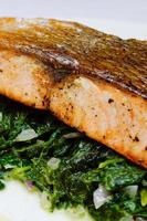 Salmon steak on spinach, selective focus