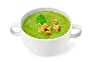 Soup puree with croutons and spinach in bowl