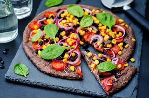 pizza de corteza de frijoles negros con maíz, espinacas, tomates y frijoles negros