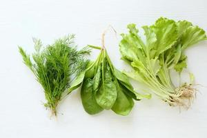 dill, spinach and lettuce on white wooden background