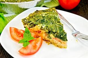 Pie celtic with spinach and tomatoes on table photo