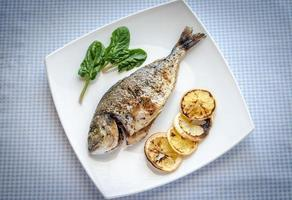 Grilled dorada fish with lemon and spinach photo