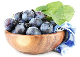 Ripe sweet plums in wooden bowl, isolated on white photo