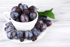 Ripe sweet plums in big cup, on grey wooden table photo