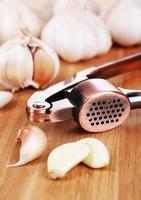 Garlic press on wooden background