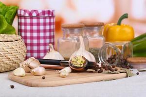 composición con prensa de ajo, ajo fresco y frascos de vidrio foto