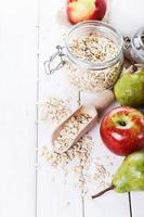 Fruits and oats over white wooden background photo