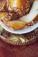 Caramelized pear dipped with peanuts decorated with golden leaves