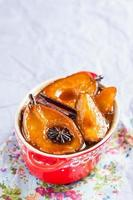 Warm dessert with caramelized pears in red pot