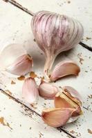 Bulbos de ajo y dientes sobre tabla de tabla de pintura descascarada foto